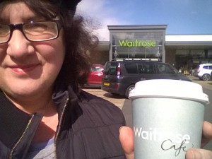 Photo of Debbie Young with coffee outside store