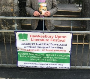 photo of Hugh Arthur holding his book by the Festival sign