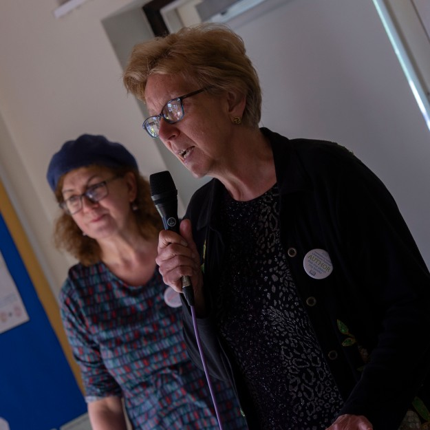 photo of Shirley Wright speaking at the opening ceremony with Debbie Young