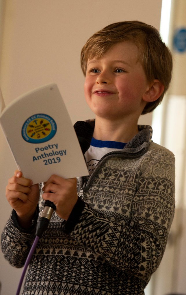 photo of small boy proudly reading his poem